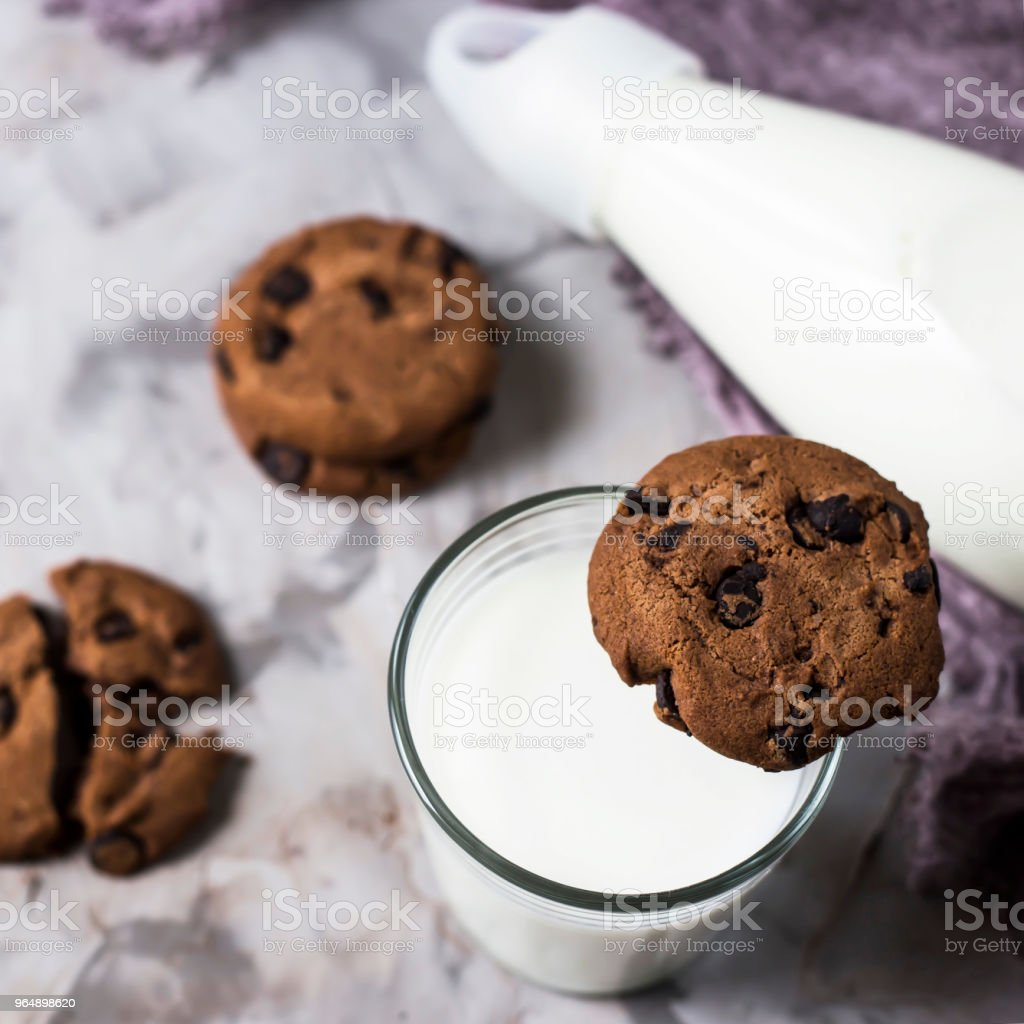 Chocolate biscuits next to a glass bottle and a glass of milk on a gray table. Top view, flat lay royalty-free stock photo