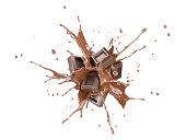 Chocolate blocks splashing into a liquid chocolate splash burst in the air. Isolated On white background.