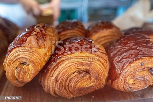 Close-up of several pain au chocolat, or chocolate croissants, a breakfast pastry, on a rustic wooden surface, October 6, 2019