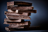 Chocolate broken on a stack, on a dark background.