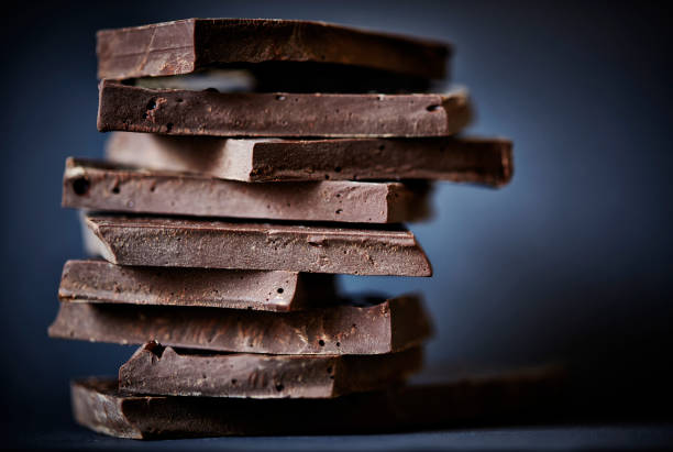 Chocolate broken on a stack on a dark background. stock photo
