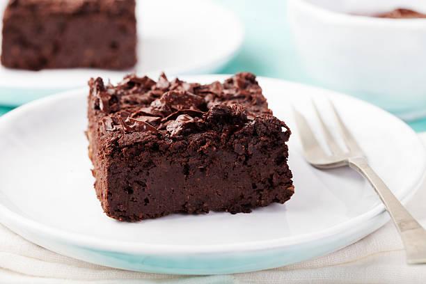 brownie al cioccolato, torta, un piatto bianco su sfondo in legno turchese - foto stock