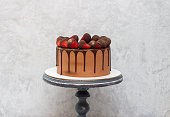 Chocolate brownie cake with strawberries dipped into melted chocolate. Grey marble cakestand, light grey background. Copy space.