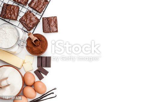 Top angle view of ingredients for preparing homemade chocolate brownies arranged at the left of an horizontal frame leaving useful copy space for text and/or logo. Ingredients included in the composition are butter, sugar, flour, eggs, chocolate bars and salt. Various baked brownies are at the top placed in a cooling rack. Predominant colors are brown and white. High key DSRL studio photo taken with Canon EOS 5D Mk II and Canon EF 70-200mm f/2.8L IS II USM Telephoto Zoom Lens
