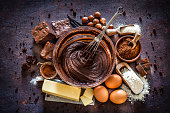 Top view of dark kitchen table filled with ingredients for preparing homemade chocolate brownies. The composition is arranged at the center of the frame. A large mixing bowl filled with chocolate spread mix and a wire whisk is at the center and all around it are other ingredients like butter, powdered cocoa, sugar, flour, eggs, chocolate bars salt and hazelnuts. Predominant color is brown. Low key DSRL studio photo taken with Canon EOS 5D Mk II and Canon EF 100mm f/2.8L Macro IS USM.