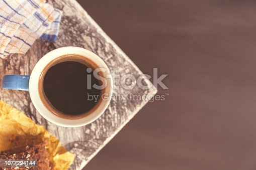 Chocolate brownie sprinkled with cocoa and coconut in the background with a coffee mug on the corner of a table near a window. Stock photo