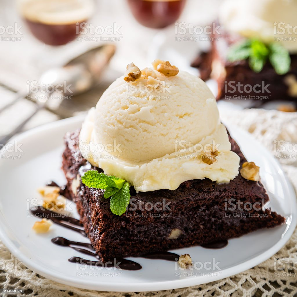 Chocolate brownie with vanilla ice cream, nuts and mint stock photo
