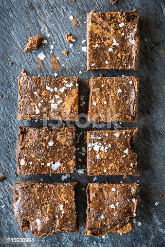 Freshly baked chocolate brownies sitting on a grey slate background. Salt flakes are scattered across the brownies. One has been taken, leaving an empty space and crumbs.
