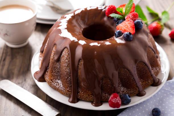 schokoladen gugelhupf mit beeren - schokoladen biskuitkuchen stock-fotos und bilder