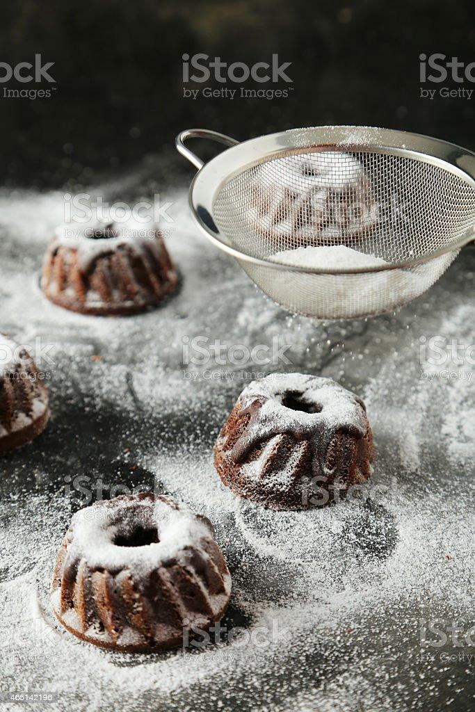 Chocolate bundt cakes with icing sugar on black background stock photo