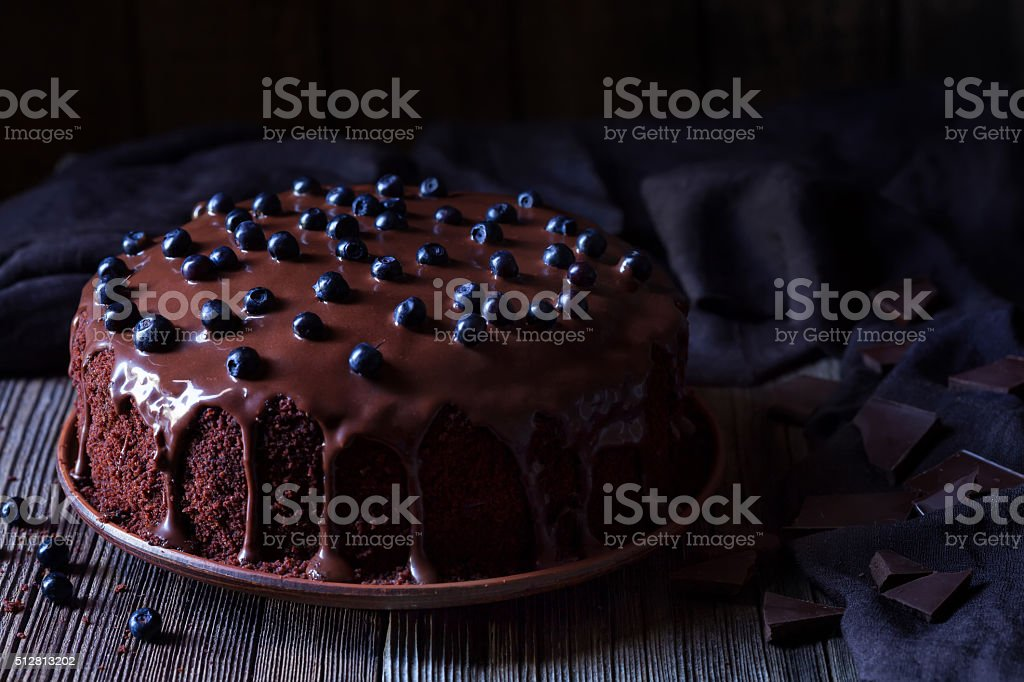 Chocolate cake decorated with blackberries on vintage wooden table background stock photo