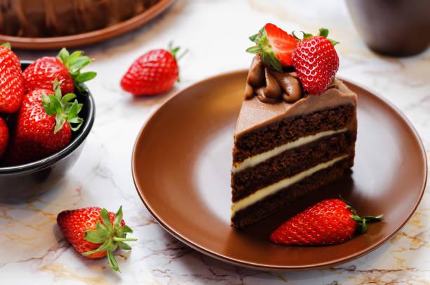 schokoladenkuchen mit erdbeeren verziert - schokoladen biskuitkuchen stock-fotos und bilder