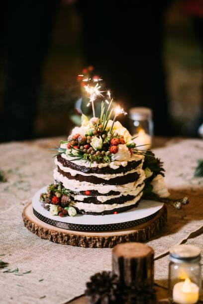 schokoladenkuchen auf tisch mit blumen, hochzeitstorte mit rosen schlagsahne - hausgemachte hochzeitstorten stock-fotos und bilder