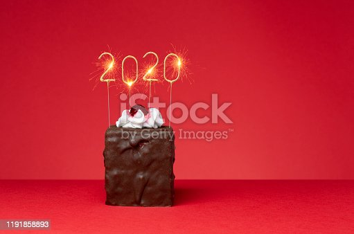 Chocolate cake with candied fruit and whipped cream and sparkler in a  new year shape isolated on red background