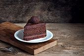 Piece of Chocolate Cake on white plate on wooden background. Homemade chocolate cake.