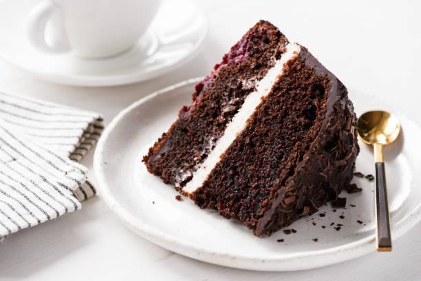 schokoladenkuchenscheibe auf weißem teller - schokoladen biskuitkuchen stock-fotos und bilder
