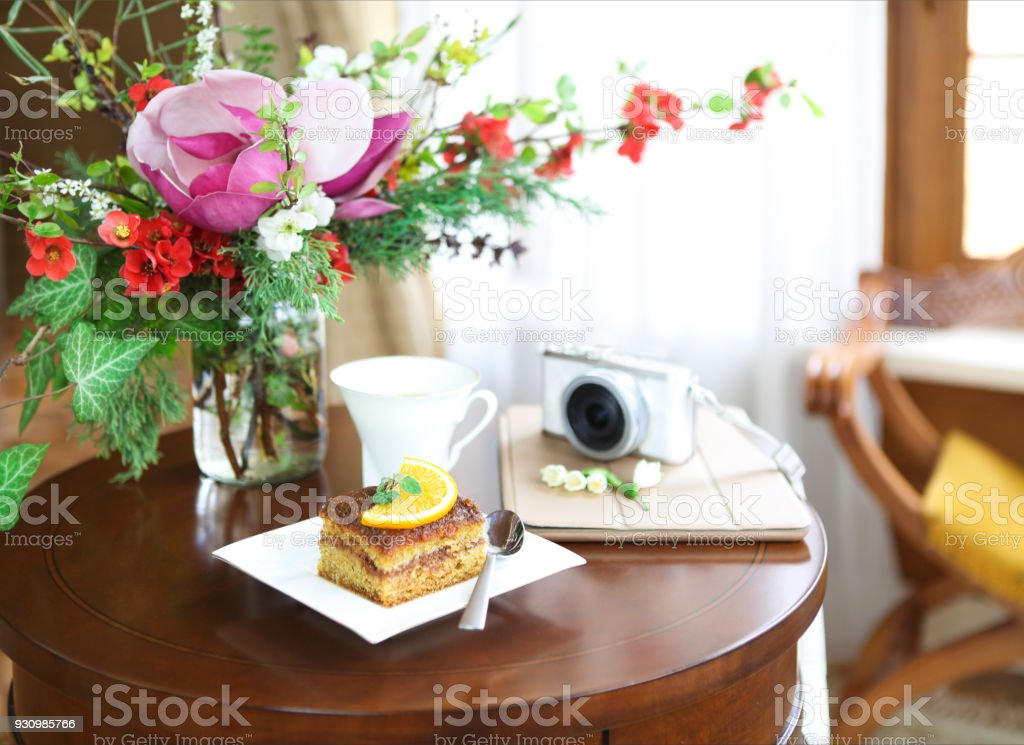 Chocolate cake, tea, tablet computer, camera and bouquet of blossom spring flowers