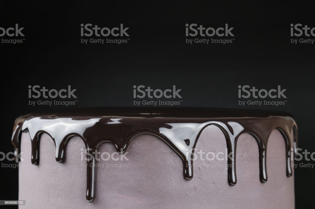 Chocolate cake with black glaze on a black background. Picture for a...