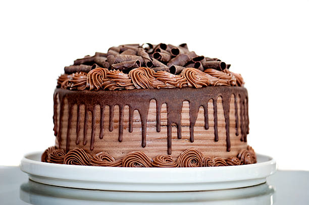Chocolate Cake with Chocolate Fudge Drizzled Icing and Chocolate Curls Chocolate Cake with Chocolate Fudge Drizzled Icing and Chocolate Curls on White Backdrop cake stock pictures, royalty-free photos & images