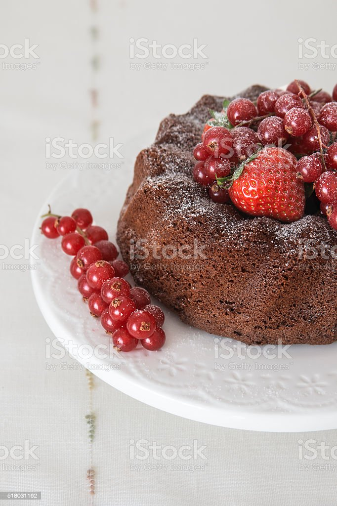 Chocolate cake with fresh berries set in a white tableware stock photo