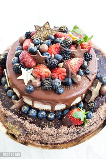 472311978 istock photo Chocolate cake with icing, decorated fresh fruit 535514459