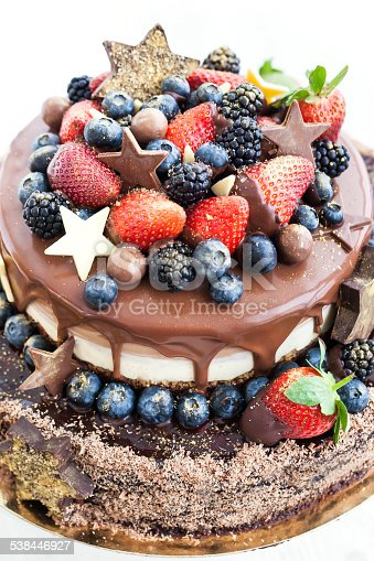 472311978 istock photo Chocolate cake with icing, decorated fresh fruit 538446927