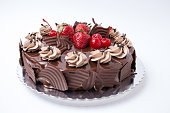 A gourmet chocolate cake with chocolate icing and chocolate shavings, in five images including a whole cake, a cake with one piece missing, the top of the cake, a closer look at the intricate icing, and one piece of cake on a white plate with fork with a floral table cloth background.