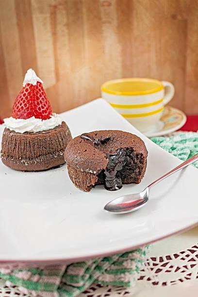 schokolade kuchen mit erdbeeren in der form der hut, weihnachten - weihnachtsmannhüte aus erdbeeren stock-fotos und bilder