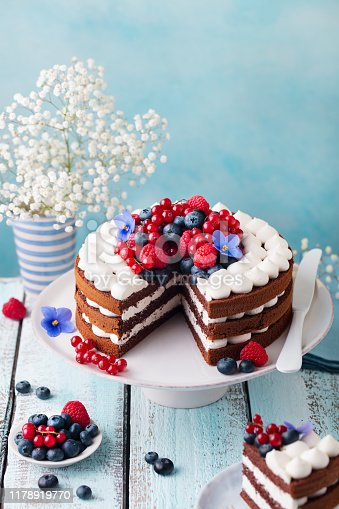 Chocolate cake with whipped cream and fresh berries. Blue wooden background. Copy space