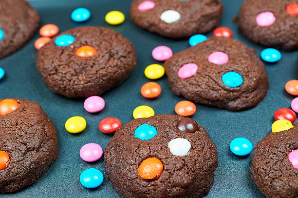 Chocolate cakes made by children. Cookies with colorful candies stock photo