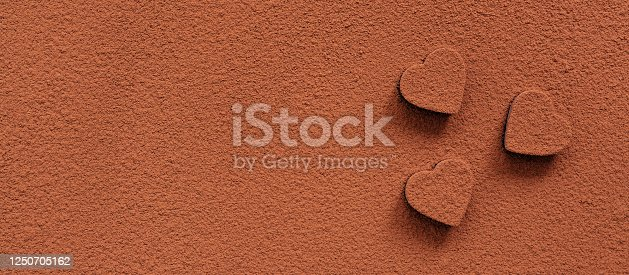 Chocolate candies heart sprinkled with cocoa powder. Abstract background.Valentines day. Cocoa texture. View from above