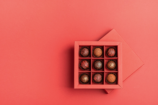 Chocolate candies in a red craft box on a bright coral background. Flat layout . Holiday Concept