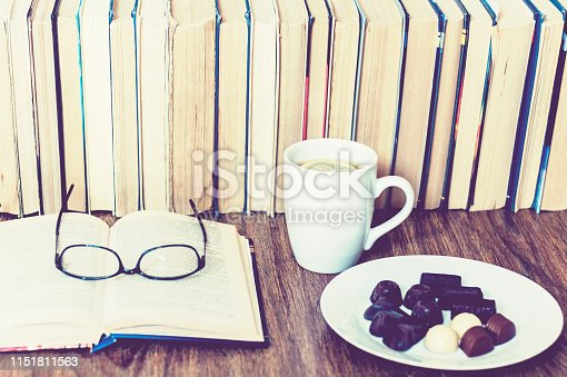 istock chocolate candies on white plate  and cup of tea with lemon with Stack of books on the background 1151811563