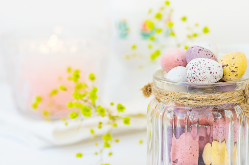 Chocolate Candy Multi-Colored Small Quail Easter Eggs Pastel Colors in Vintage Glass Jar Tied with Twine on White Wood Table Yellow Spring Flowers Lit Candle Copy Space Festive Setting