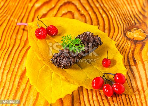 istock chocolate candy on autumn leaf, with red currants 889166102