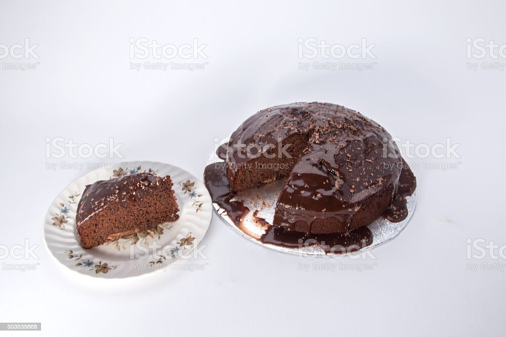 Chocolate caramel cake iced with a slice cut out stock photo