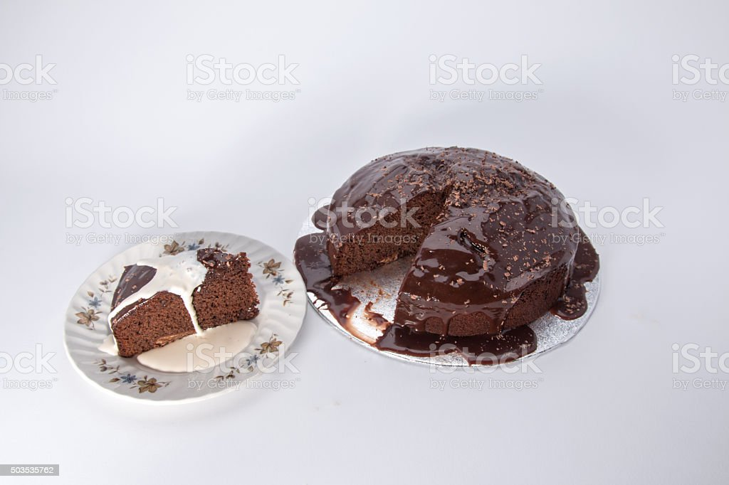 Chocolate caramel cake with a slice cut out and cream stock photo