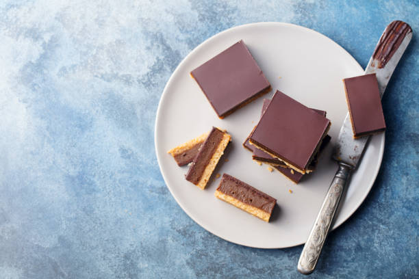 Chocolate caramel slices, bars, millionaires shortbread on a grey plate. Blue background. Top view. - fotografia de stock