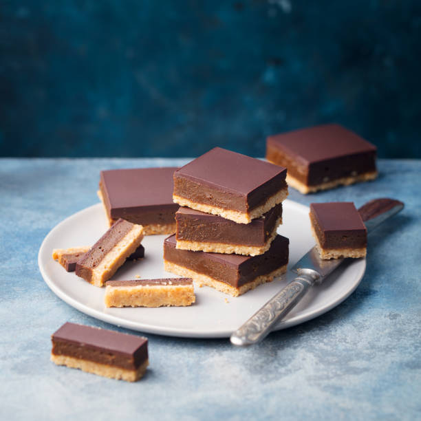 Chocolate caramel slices, bars, millionaires shortbread on a plate. Blue background. Copy space. Chocolate caramel slices, bars, millionaires shortbread on a plate. Blue background. Copy space millionnaire stock pictures, royalty-free photos & images