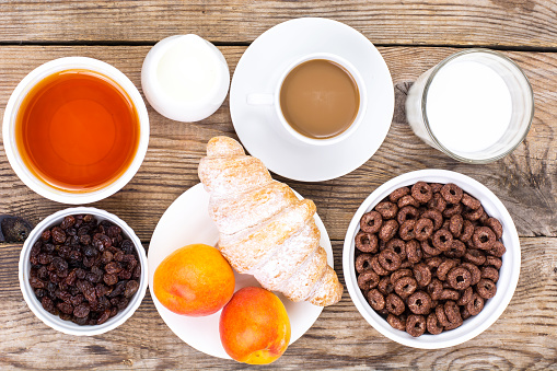 840939766 istock photo Chocolate cereal flakes, coffee, milk, croissant and fruit for b 816303238