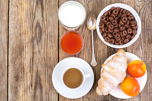 840939766 istock photo Chocolate cereal flakes, coffee, milk, croissant and fruit for b 816303510