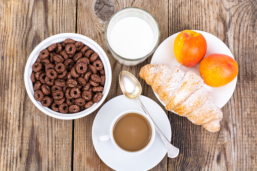 840939766 istock photo Chocolate cereal flakes, coffee, milk, croissant and fruit for b 816305338