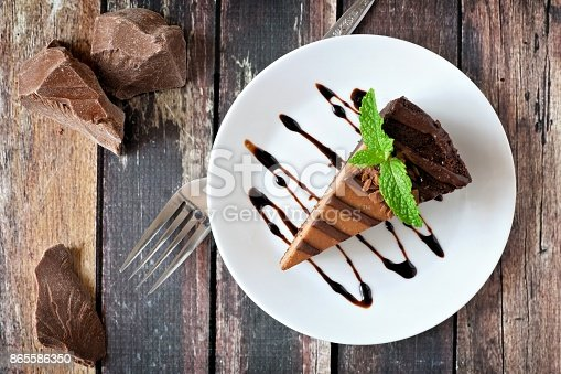 Slice of chocolate cheesecake on plate, above view over a rustic wood background