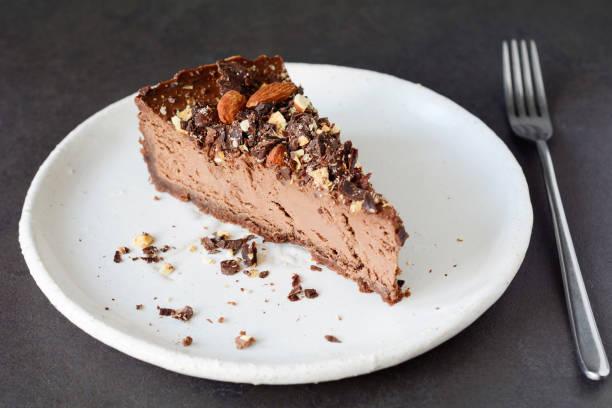 schokoladen-käsekuchen slice auf weißen teller - schokoladen käsekuchen törtchen stock-fotos und bilder