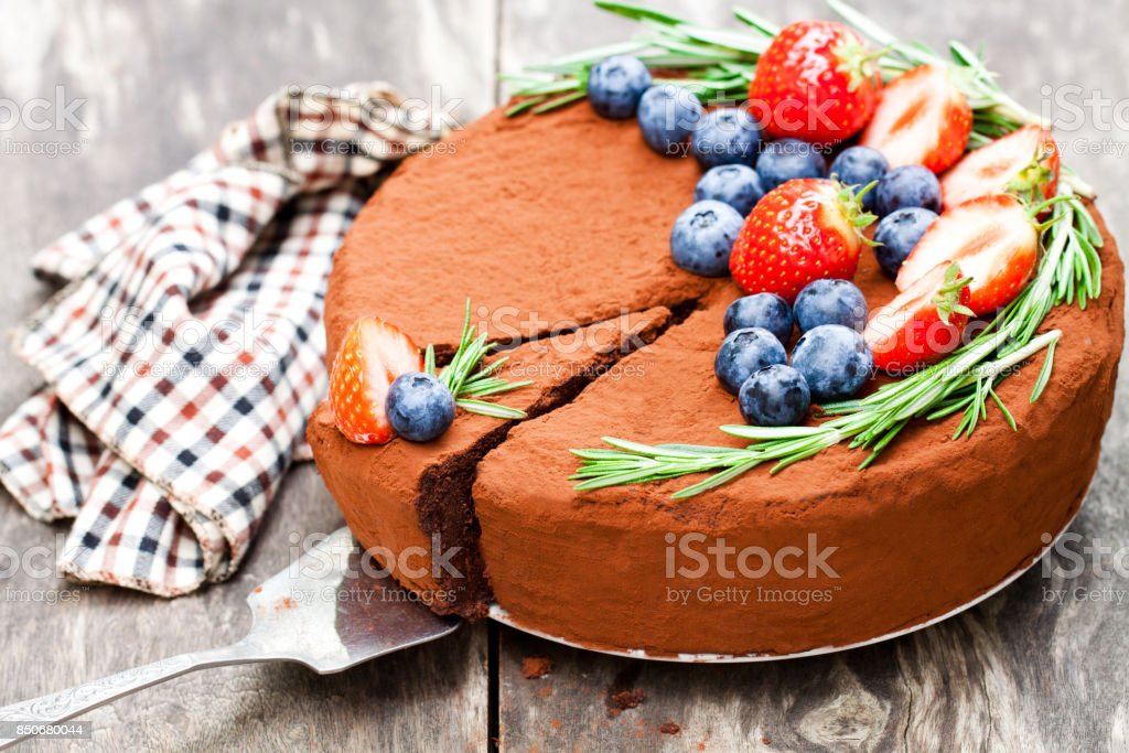 Chocolate  cheesecake with berries on wooden background stock photo