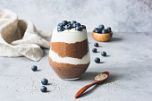 Chocolate Chia Seed Pudding In Glass Topped With Blueberries On Concrete Background