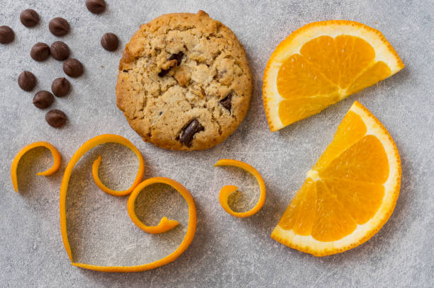 Chocolate chip and orange cookie. Orange peel in a heart shape on grey stone background. stock photo