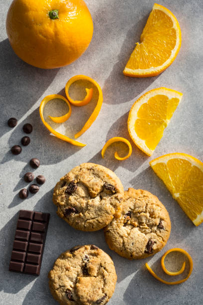 Chocolate chip and orange cookie. Orange peel in heart shape on grey stone background. stock photo