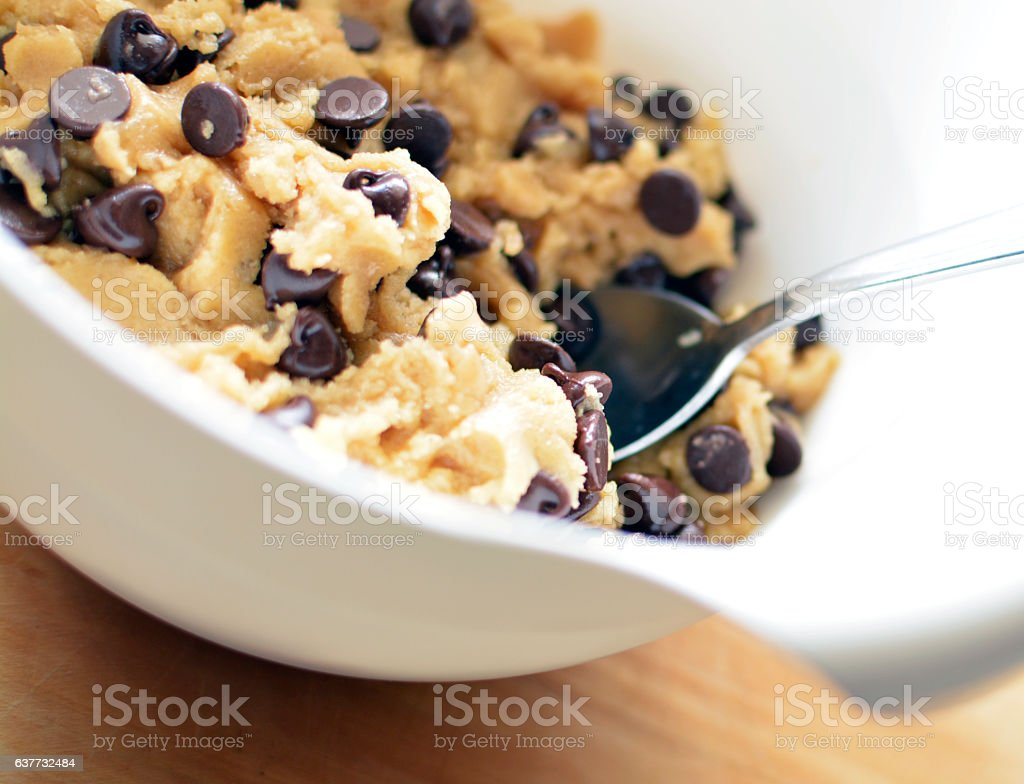 Chocolate Chip Cookie Dough in mixing bowl with spoon stock photo