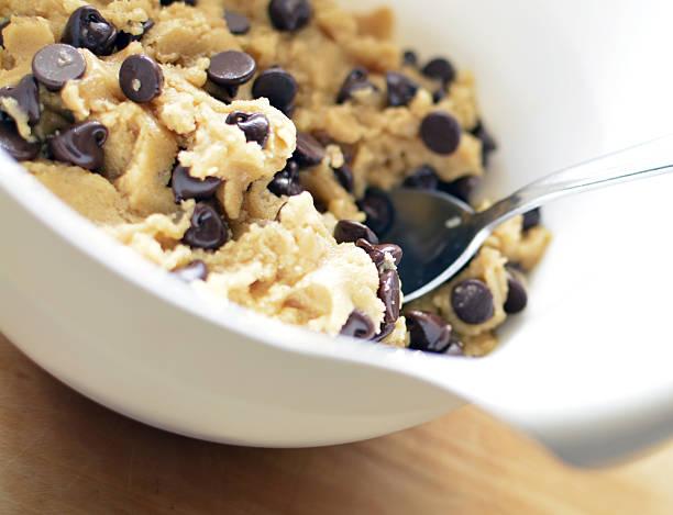 chocolate chip cookie dough in mixing bowl with spoon - impasto per il pane foto e immagini stock